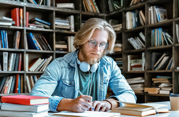 Concentrated bearded young man student teacher hipster glasses sit study library desk hold pen make notes from book hand write essay notebook fill in journal do homework make report education concept.