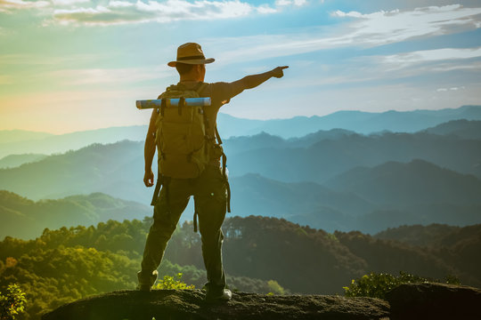 Young Man standing alone in forest outdoor with sunset nature on background Travel Lifestyle and survival concept.