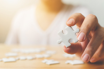 Hand of male trying to connect pieces of white jigsaw puzzle on wooden table. Healthcare for alzheimer disease, dementia, memory loss, autism awareness and mental health concept Wall mural
