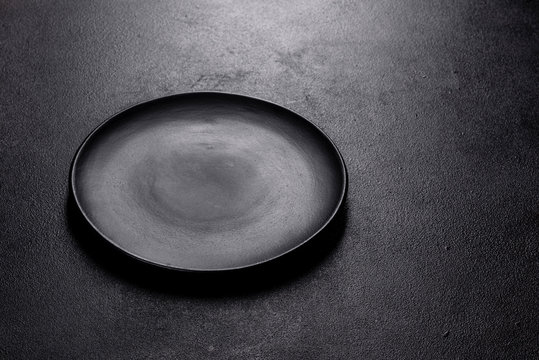 Empty black plate over dark stone background with free space