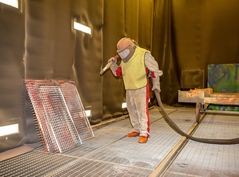 the worker processes the sandblast in the chamber dirty part before painting