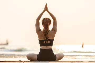 Back of views woman practice yoga lotus pose to meditation with summer vacation on the beach feeling so happiness and cheerful,Travel in tropical beach in Thailand,vacations and relaxation Concept