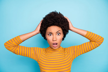 Fototapete - Closeup photo of pretty stupor dark skin curly lady listen awful news open mouth unexpected epic fail arms on head wear yellow striped jumper isolated blue color background