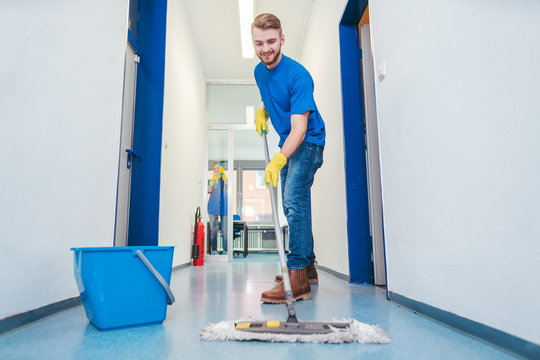 Cleaner man mopping the floor in a hall