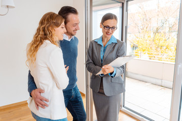Landlady or realtor showing lease agreement to new tenants