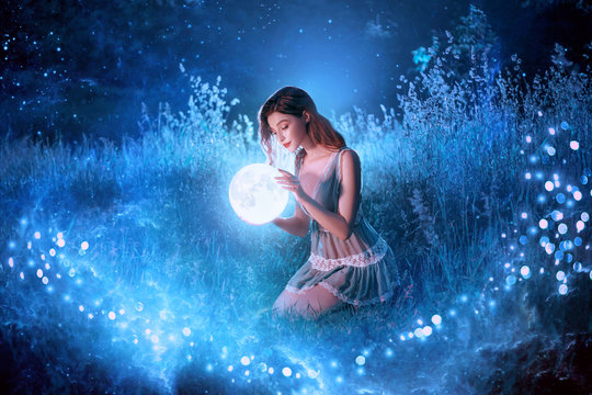 Fairytale sorceress holds in hands magical ball planet universe space sitting in night forest. Goddess with long red hair in short sexy blue dress. Backdrop flying bright sparkle stars white grass fog