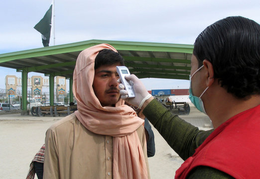 A health worker takes the temperature of a man, who returned from Afghanistan, for a medical observation as a preventive measure following the coronavirus outbreak, near the Friendship Gate, crossing point at the Pakistan-Afghanistan border town of Chaman