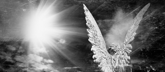 Wall Mural - Rear view of an angel with wings in the rays of light. Antique statue. Black and white image.