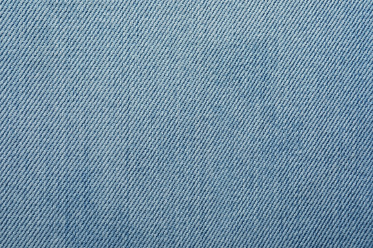 Texture of light blue jeans as background, closeup