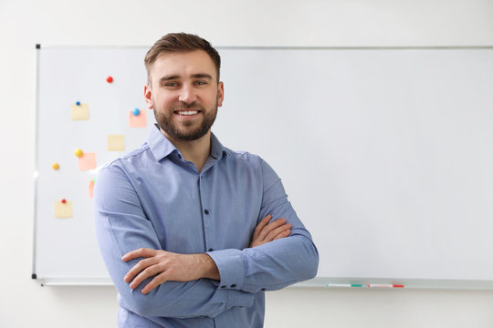 Portrait of young teacher near whiteboard in classroom