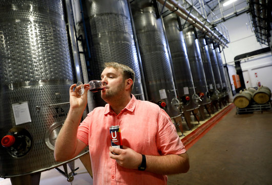 Uncanny Wines co-owner Arnold Vlok samples a glass of Merlot, part of a the company's series of canned wines, in Paarl