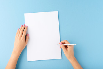 Overhead shot of female hands writing with pen over empty white sheet of paper on blue background