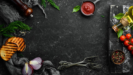 Fotomurales - Cooking banner. Vegetables and spices on a black background. Free space for your text. Rustic style.