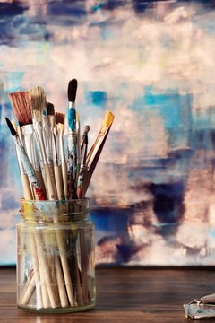 Paint brushes and abstract artwork on canvas