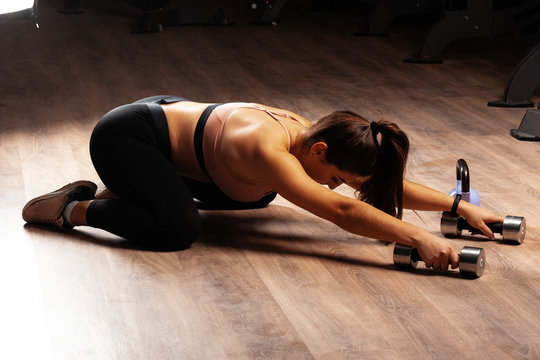 Brunette woman plus size model doing stretching exercises in a dark gym
