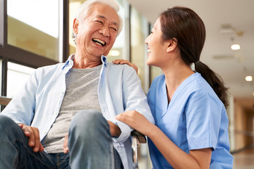 young friendly asian female caregiver talking to elderly man in nursing home Fotomurales
