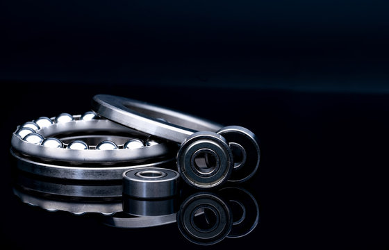 Stainless steel thrust ball bearing. Set of thrust ball bearing and shiny silver ball bearing. Spare parts for roller machine in heavy machinery and automotive industry. Round metal wheel.