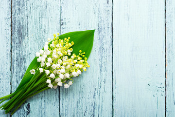 Photo sur Aluminium Muguet de mai bunch of lily of the valley flowers on faded blue table, directly above
