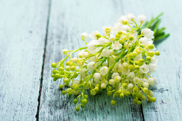 Photo sur Aluminium Muguet de mai bunch of lily of the valley flowers on faded blue table