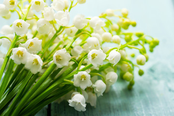 bunch of lily of the valley flowers on faded blue table