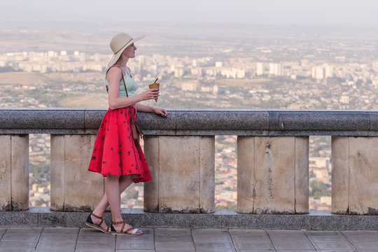 Young woman in hat and with ice cream in hand. Viewpoint overlooking the panorama of the city