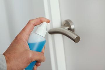 man disinfecting the door handle