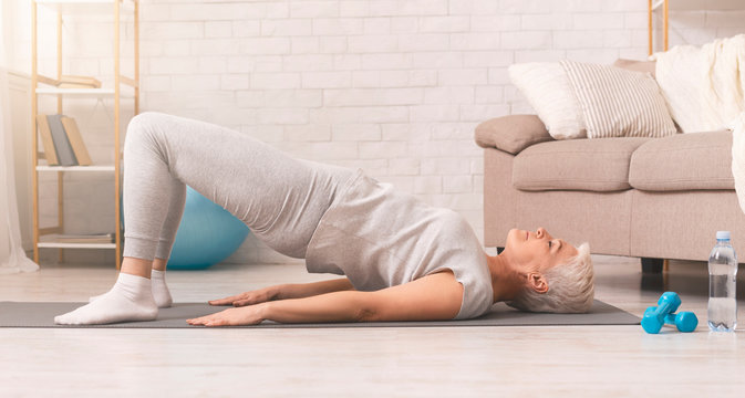 Active senior woman doing back exercise on floor at home