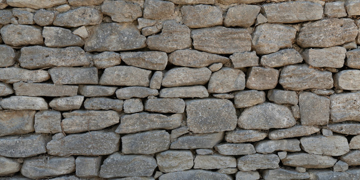 Old Grey stone wall made of large gray small rectangular hewn natural stones