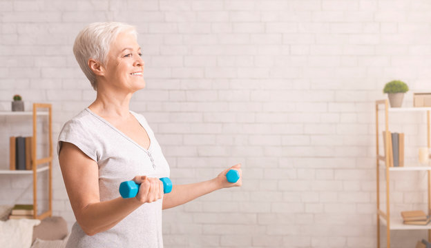 Sporty senior woman exercising with dumbbells at home