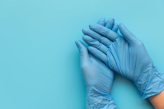 Hands of medic wearing blue latex gloves on blue background. Protection concept