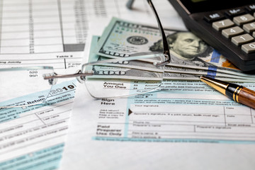 1040 income tax return form 2019 with calculator, money, and pen. Focus through glasses on amount you owe. Concept of filing taxes, payment, refund, and April 15, 2020 tax deadline