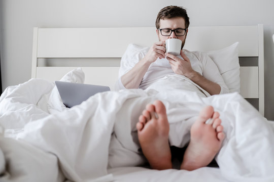 Relaxed man, in pajamas, drinks aromatic coffee, sits in bed with his feet out from under the covers, a laptop lies nearby.
