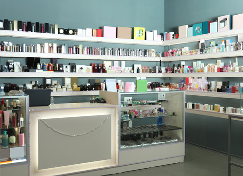 Counter and shelves with perfume bottles in shop