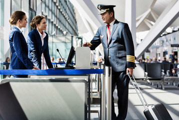Fototapeta Portrait of mature pilot talking with the airport staffs in boarding gate obraz