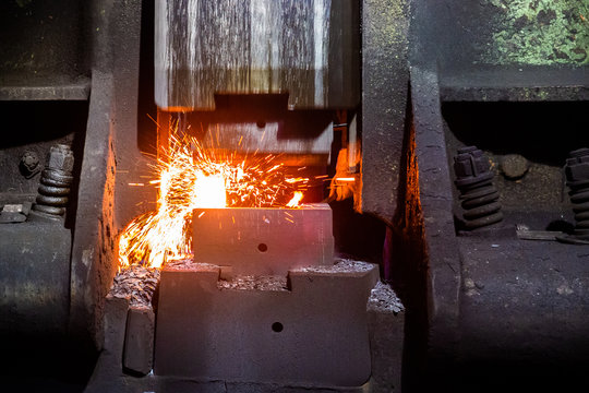 close-up frontal view of hot steel forging process with big mechanical hammer machine