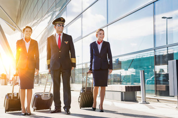 Mature pilot with young beautiful flight attendants walking in airport