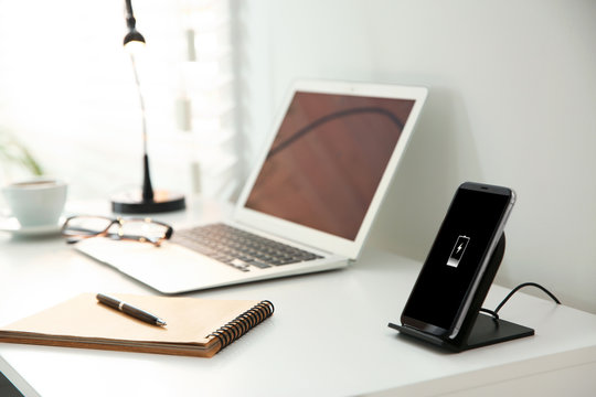 Mobile phone with wireless charger on white table. Modern workplace accessory