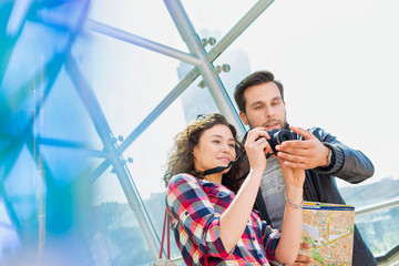 Portrait of young attractive couple looking on their pictures in the camera