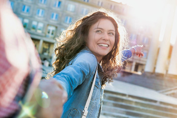 Portrait of young beautiful woman smiling and walking while holding her boyfriend hand