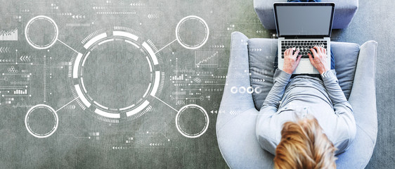 Tech circle with man using a laptop in a modern gray chair Wall mural