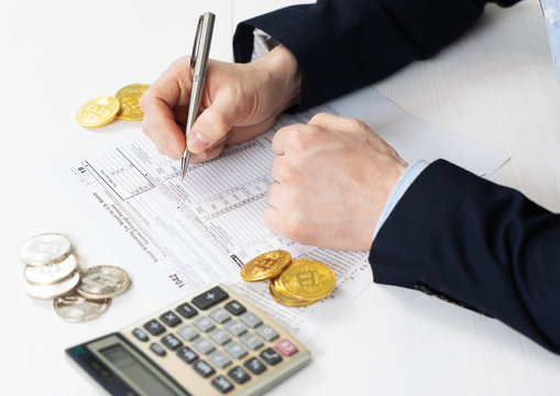 Taxation: a man in a jacket fills out a tax return on trading income on a cryptocurrency exchange.