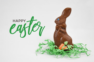 Wall Mural - Happy Easter Greeting Card Text With Chocolate Easter Bunny Candy and Green Grass Isolated Over White Background
