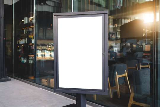Mock up front view blank billboard advertising in black frame with clipping path standing in restaurant.