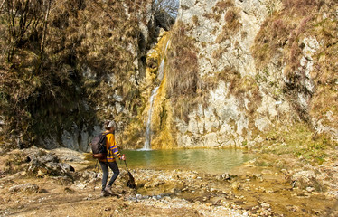 Female hiker arrives and admires a waterfall with a beautiful puddle of water