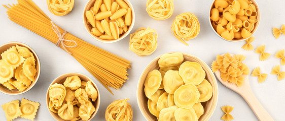 Flat lay with different types of traditional italian pasta. Penne, tagliatelle, fusilli, farfalle, spaghetti and others. Traditional italian cusine concept. Top view Fototapete