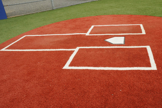 close up of a baseball or softball turf field batters box and home plate