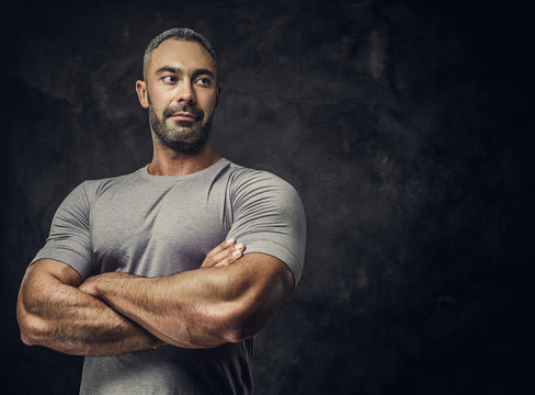 Strong, adult, fit muscular caucasian man posing for a photoshoot in a dark studio under the spotlight wearing grey sportswear, showing his muscles with arms crossed, looking confident and calm