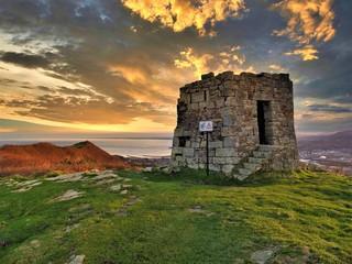 Torre del monte Jaizkibel en un atardecer con Honarribia al fondo Fotomurales
