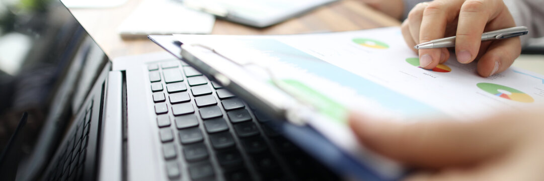 Group of people working with financial reports clipped to pad at workplace closeup