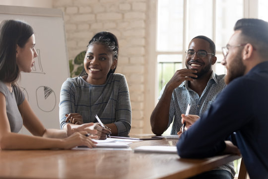 Multi racial employees listening ceo at group meeting